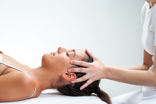 A chiropractor works a lady's head.